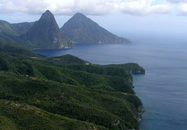 "Twin Pitons (Petit and Gros) - are the eroded spire shaped remnants of two lava domes formed on the flanks of a larger and collapsed strato (composite) volcano<br /> - which is composed of ""andesitic"" lava (also called, ""intermediate lava""), an extrusive igneous rock, whose composition is lower in aluminum and silica, and usually somewhat richer in magnesium and iron - this lava's molten magma temperature ranges from about 1400  to 1750 °F (750 - 950 °C), and has a rather high viscosity (thus resulting in the steepness of its flow and layering formation)"