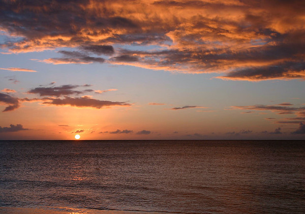 Sunset glow across the Caribbean Sean and stratus clouds, from Dorsch Beach - western coastline of the island