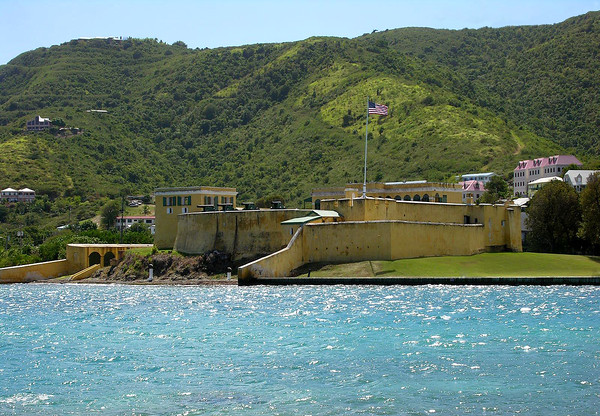 """Fort Christiansvaern (meaning christian defense) - occupied and strengthened by the Danish in 1738 (but the earthen structure was destroyed by a hurricane), and replaced in 1749 by this masonry fort (measuring 210 by 225 ft. - 64 by 69 m), to protect the harbor at the town of Christiansted - which from 1734 until 1803, was part of the infamous """"Triangular Trade"""" - where slaves were acquired for cheap manufactured goods at slaving forts, along the Guinea Coast of West Africa, and shipped to the West Indies - here they were auctioned off, and the ships cargoes replenished with local exports bound for Europe and North America."""