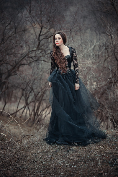 Beautiful girl with long hair standing in a black dress standing on the gothic background blowers forests, forest princess, halloween , dark boho , fashionable toning , creative color