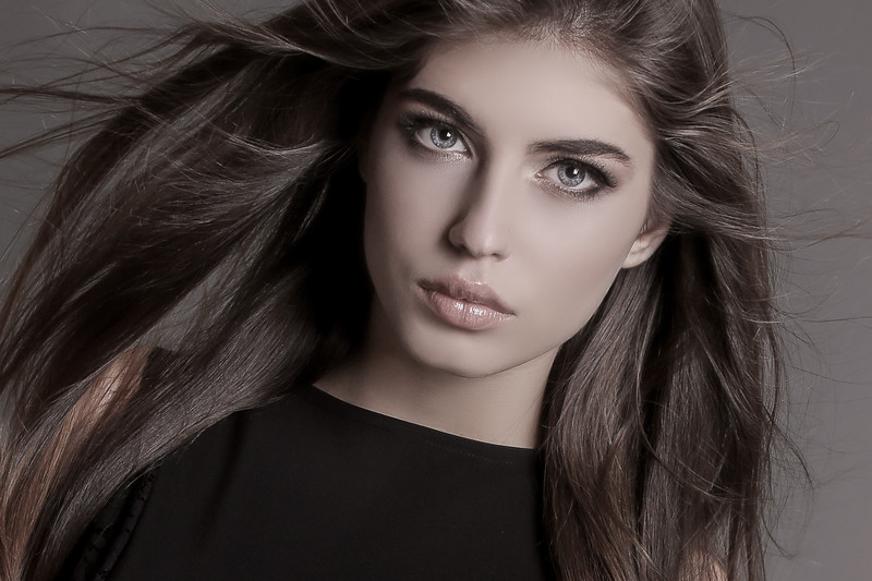 gorgeous sensual woman with dark straight hair wears elegant clothes