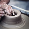 Hands working on pottery wheel ,  artistic  toned
