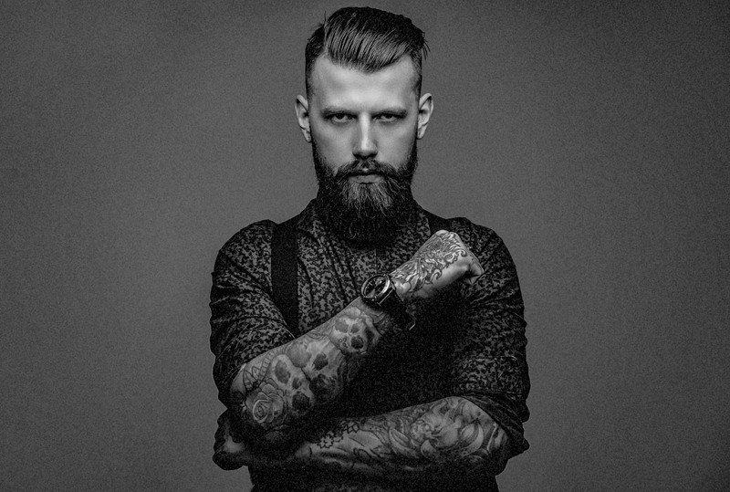 Handsome old-fashioned hipster in shirt and suspenders, pose wit