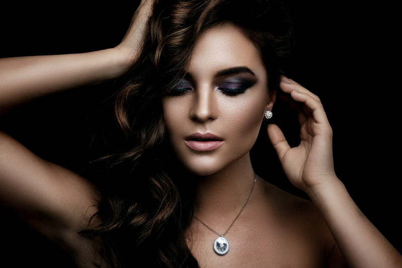 Woman with curly hair, beautiful make-up and expensive pendant with a dimond