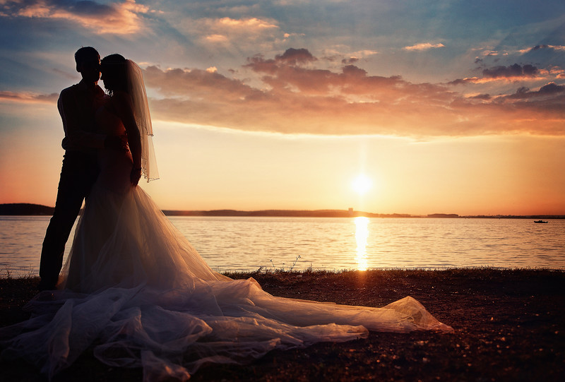 bride and groom together on a background sunset