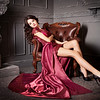 Woman sitting in chair in long claret, purple dress. Luxury