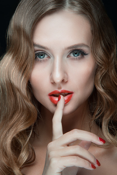 Portrait of beautiful young women with red lips, wavy hair, black eyeliner. Beauty. Studio shot. Black background.