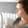 Woman with cup of coffee or tea in kitchen