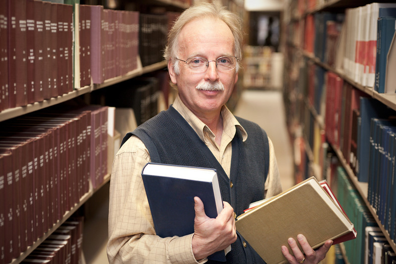 """Professor in a library. <a href=""""http://www.istockphoto.com/file_search.php?action=file&lightboxID=5540504"""">Available for purchase from William Britten iStockphoto</a>"""