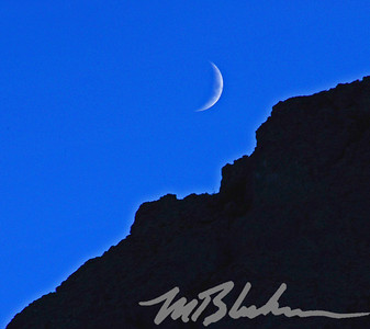 Crescent Moon Above Silouetted Mountain Top