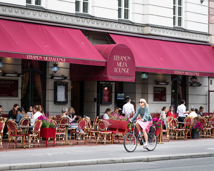 Her skirt matches the cafe awning.  Stockholm, Sweden