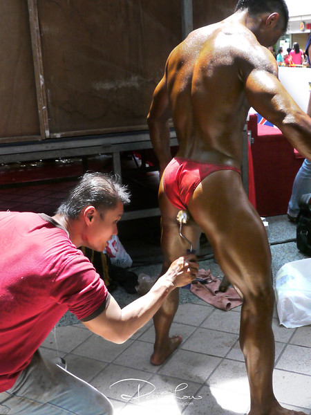 Tickling his testicles - - His assistant was using a typical paint roller to smudge off his sweat in preparation for the body building competition.
