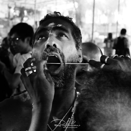 A priest piercing a skewer to a devotee.