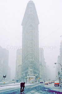 Bike commuter passing New York's Flatiron Building during snowstorm