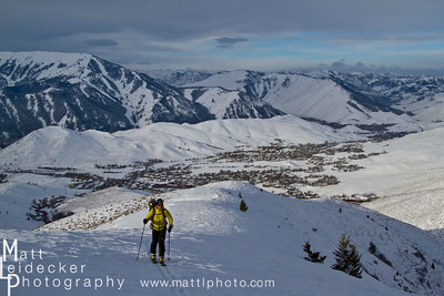Backcountry skier hikes up a ridge with Sun Valley's Bald Mountain in the background.