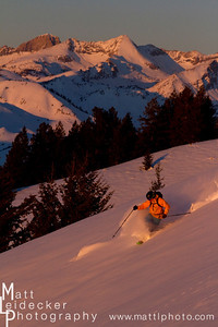 backcountry skiier skiing in the pink sunset light with the Devils Bedstead (11865 feet) Slazburger Spitzl (11540 feet), model release.