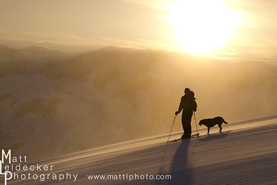 Skiier and his dog resting on an early morning run on Sun Valley's Bald Mountain.