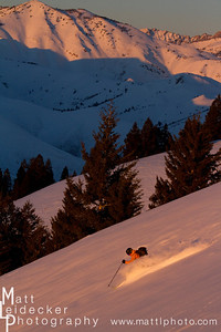 backcountry skiier skiing in the pink sunset light with johnstone peak (9949 feet) in the background.  model release