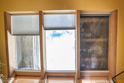 This looking from the floor of the sunroom directly up at the ceiling.  The pane on the right is shattered completely (the outside of a double pane sheet) and covered with a sheet of plywood on the exterior.  The middle and left windows both have cracks in the outside layer.