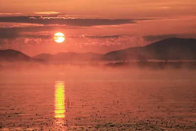 The sun rises over Raquette Lake in the Adirondack Mountains