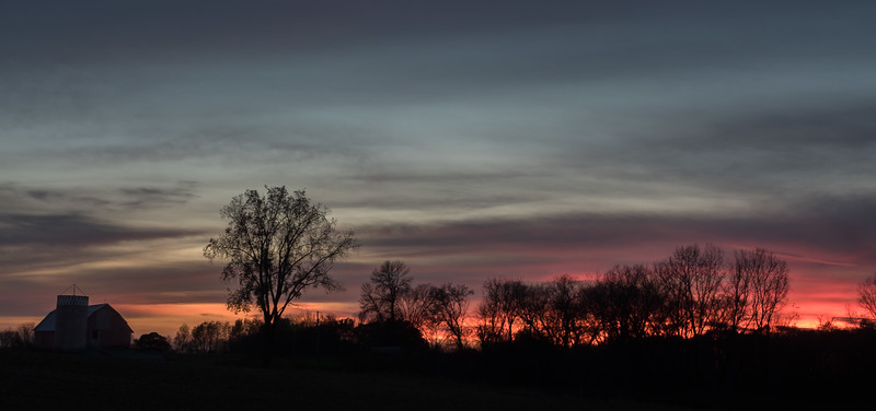 Farm Silhouetted By the Setting Sun