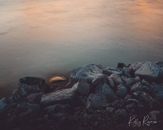 A long lasting golden hour on the lake. Rocks catching the slow crashing waves.