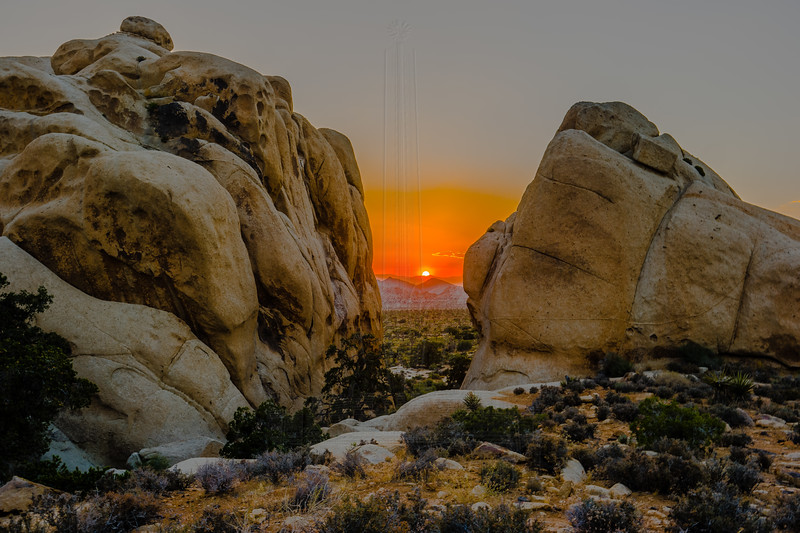 The sun setting between two rocks.