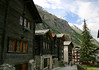 Transition from the stone-roofed wooden dwellings - to the stucco shingled roof dwellings - with the mountain streams flowing along the rocky slopes of the Matter Valley - canton of Valais