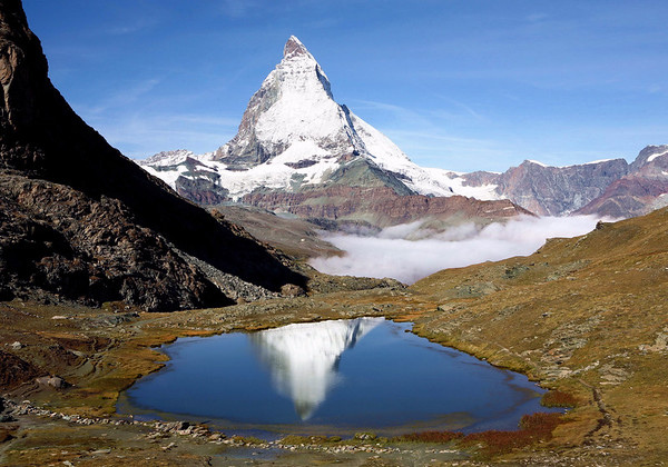 Reflection of the eastern face summit of the Matterhorn - in the alpine lake of Riffelsee - along the lower partially shaded slop of the Riffelhorn - canton of Valais