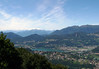 Northeast view from atop Monte Salvadore - beyond the small lake of Muzzano - to the distal cloud covered peaks of the western Alps under the cirrus clouds.