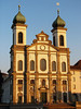 Day's last sunlight upon the baroque style facade and oxidized copper spires atop the twin towers of the Jesuitenkirche (Jesuit Church) - as a pair of swans swim along the Reuss River - Lucerne
