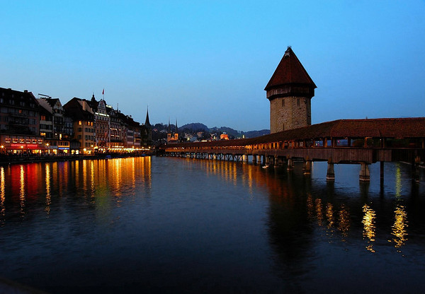 Dusk upon the Reuss River - with the Alstadt (old city) - Kapellbrücke (Chapel Bridge) and Wasserturm (Water Tower) - the twin towers and spires of the Hof Church (beyond the bridgehead) - and the distal illuminated, Palace Luzern - Lucerne
