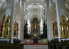 Hof Church - at the end of the main nave and last row of pews - with 4 side alters upon the corners of the crossing - with the high altar at the choir - and beyond wrought iron sculpting to the marble pillar altar piece showing the crucifix of Christ, at the apse - Lucerne