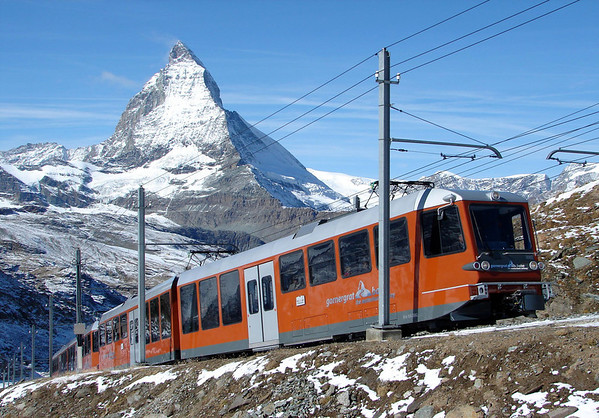 Gornergratbahn (Gornergrat Train) - the highest 10,135 ft. (3,089 m) open-air cogwheel railway in Europe - with the Matterhorn's sunlit eastern face and shaded northern face in the distance - canton of Valais
