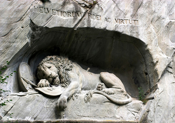 """Lion Momunemt - sculpted into the sandstone rock wall - the latin inscription HELVETIORUM FIDEI AC VIRTUTI means """"To the loyalty and bravery of the Swiss"""" - honoring the hundreds of mercenary soldiers who lost their lives when the revolutionary masses attacked the royal castle in Paris in 1792, while serving the French king Louis XVI during the French Revolution - Lucerne"""