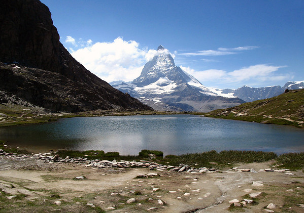 Across the Riffelsee (Riffel Lake) - to the cloud and snow-capped peak and eastern face of the Matterhorn - with the mostly shaded northern slope of the Riffelhorn adjacent to the lake - canton of Valais