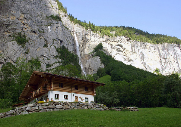 From the Lauterbrunnen Valley - to a snow-melt waterfalls, flowing down the partially shaded and sunlit limestone wall - canton of Bern