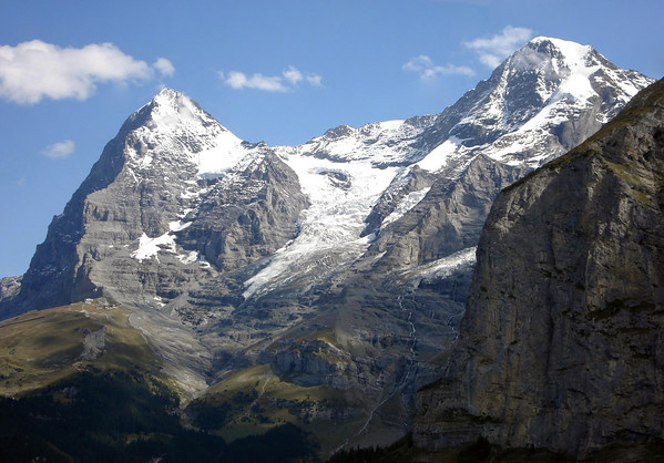 Beyond the mostly shaded limestone face of the lower Schwarzmönch - up to the summits of the Eiger and Mönch among the cumulus clouds - with the Eigergletscher (Eiger Glacier) and Clyne Eiger between - canton of Bern