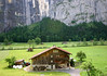 Farm houses along the Lauterbrunnen Valley - with a waterfall flowing along the sheer glacial formed limestone wall - canton of Bern