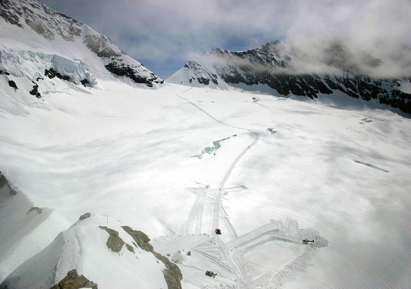 Viewing northeast from the Sphinx Observatory, at the Jungfraujoch - beyond the snowplows, igloo, helicopter, and hikers - towards the southeastern slope of the Mönch (L) - and the Trugberg (R), which is mostly covered in clouds - canton of Valais