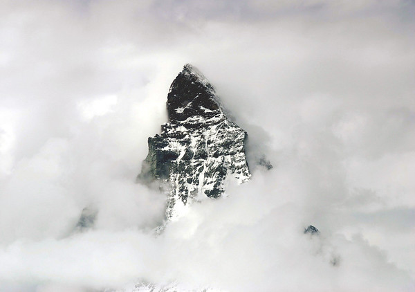 Western face and summit of the Matterhorn - surrounded by cumulus clouds