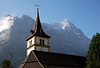 Beyond the clock tower and steeple of the Dorpkirche (Village Church) in Grindelwald - up to the cumulus cloud at the Ostegg - and the day's first sunlight upon the peak of the Eiger - canton of Bern