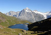 Across the Bachalpsee (Lake Bachalp), a twin level lake, along the shaded northestern slopes of the Reeti - across to the distal peaks of the Wellhorn (L), Wetterhorn (C), and Barglistock ((R) - canton of Bern