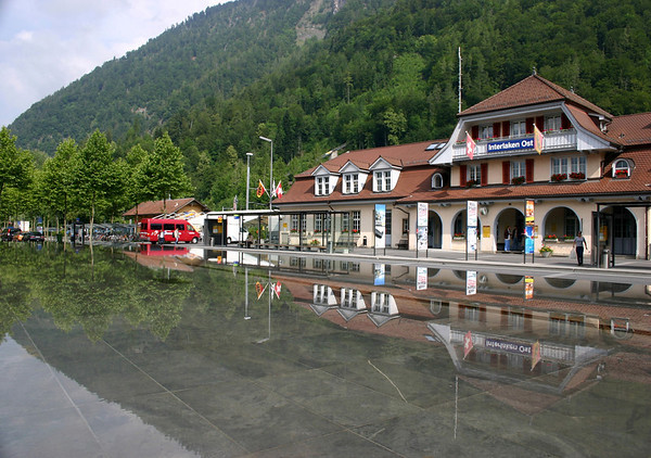 Across the reflection pool at the main rail station in Interlaken (east) - with the lower slope of the Harder Kulm behind - canton of Bern
