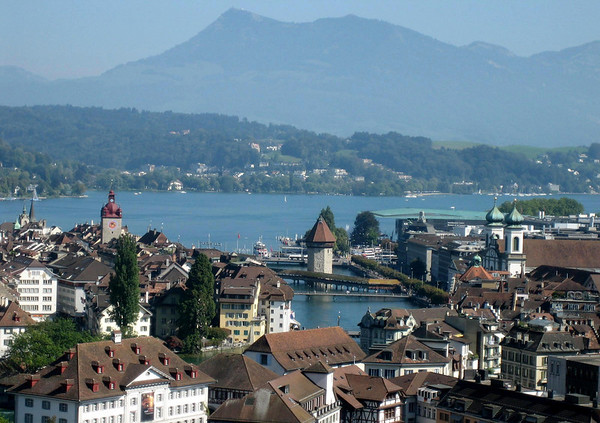 """Lucerne - Alstadt (old city) - City Hall Tower (clock tower and burgandy dome) - the covered Chapel Bridge (adjacent to the rock Wasserturm """"Water Tower"""") - the twin oxidized copper tower spires of the Jesuit Church - with Lake Lucerne beyond - and the peak of Rigi Klum, rising to 5,900 ft. (1,798 m) atop the Rigi Mountain - canton of Lucerne"""