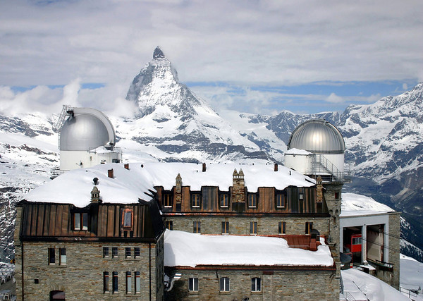 Over the snow-capped roof of the Kulm Hotel Gornergrat (the highest altitude hotel in Switzerland, at around 10,170 ft. - 3,100 m) - and the twin domes of the astronomical observatories established atop the hotel in 1967 - across to the peak of the Matterhorn - canton of Valais