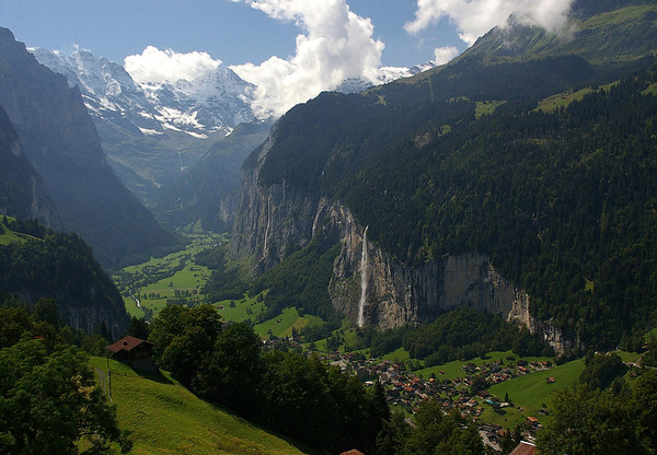 Soutward view from chynige Platte - up the Lauterbrunnen Valley - with the Staubbach Falls (1st falls on the sunlit western limestone wall), above the village of Lauterbrunnen - with several waterfalls along the sheer cliffs - as the Weisse Lütschine (river) meanders to the Schmadribach Falls, at the end of the valley - with the Grosshorn (L) and Briethorn (R ), above the falls in the cumulus clouds - canton of Bern