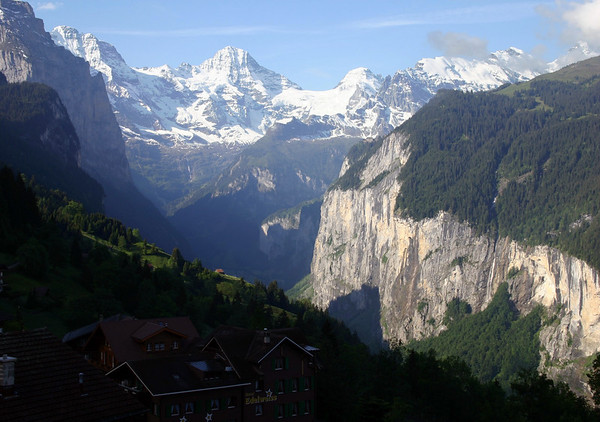 Across the shaded village of Wengen - down to the sunlit limestone Lauterbrunnen Wall, and the Staubach Falls - southward up the glacier formed valley - to the distal snow-capped peaks of the Grosshorn (beyond the shaded slope of the Mönchbüffel), Briethorn (far end of the valley), Tschingelhorn (directly beyond the end of sunlit wall), and Gspaltenhorn (far right, most covered with clouds) - canton of Bern