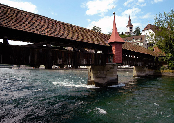 Spreuerbrücke (Mill Bridge) - originally constructed in 1408 over the Reuss River, however, destroyed by storm in 1566, and rebuilt in 1568, along with a chapel (renovated in 1889) - above the Reuss River - Lucerne - The bridge was built in the 15th century in order to connect the mills located inside the ramparts on the northern bank of the Reuss River with the baker's quarter on the southern bank of river - the bakers had to stay on the opposite river bank because they kept the fire in their stoves alive during the night, subsequently the fear that fire might destroy the whole town was not unrealistic, in fact there are no old wooden houses left today within the Alstadt (old city) of Lucerne, the exceptions are located just outside the medieval ramparts - with the Luegislandturm (tower) of that rampart seen beyond the steeple of the bridge chapel