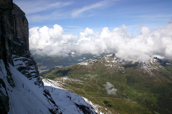 From the southern face of the Eiger - down to the alpine pass village of Kleine Scheidegg - and the Lauberhorn and Tschuggen mostly covered with cumulus clouds - and the upper western Luterbrunnen Wall, seen beyond the shaded limestone wall of the Eiger and below the clouds - canton of Bern